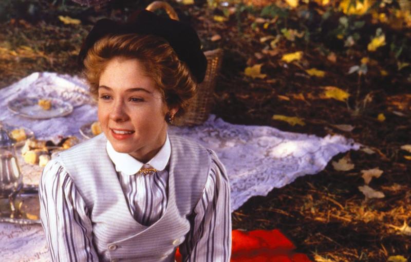 Anne egy piknik takarón ül és mosolyog
