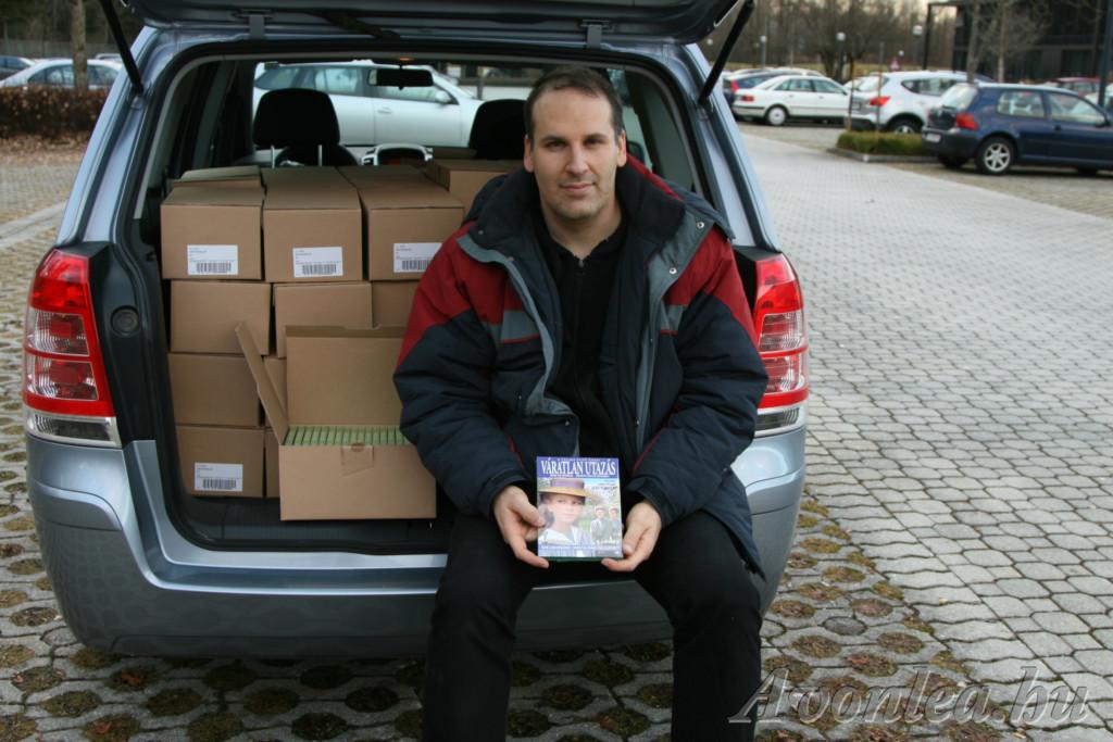 A kész Váratlan utazás-DVD-kkel pózolok egy kombi autó csomagtartójában ülve.
