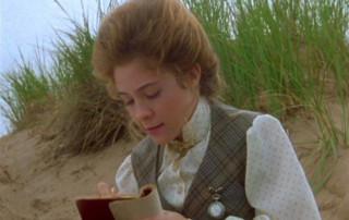 Anne egy homokdűnén ül és jegyzetel